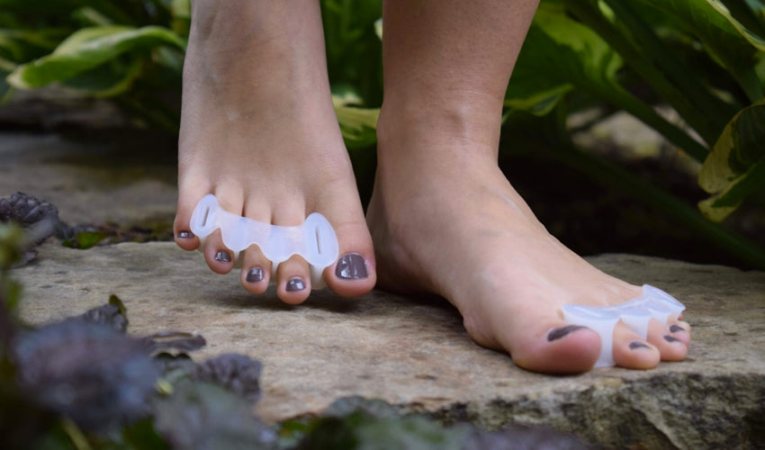 A barefooted person in a garden setting wearing Correct Toes Original toe spacers