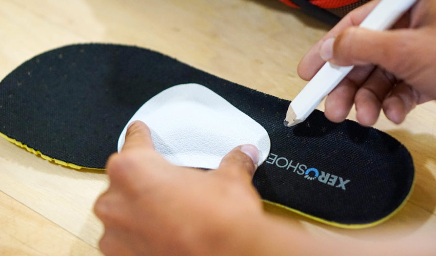 A person using a pencil to mark the optimal location for applying a Pedag metatarsal pad