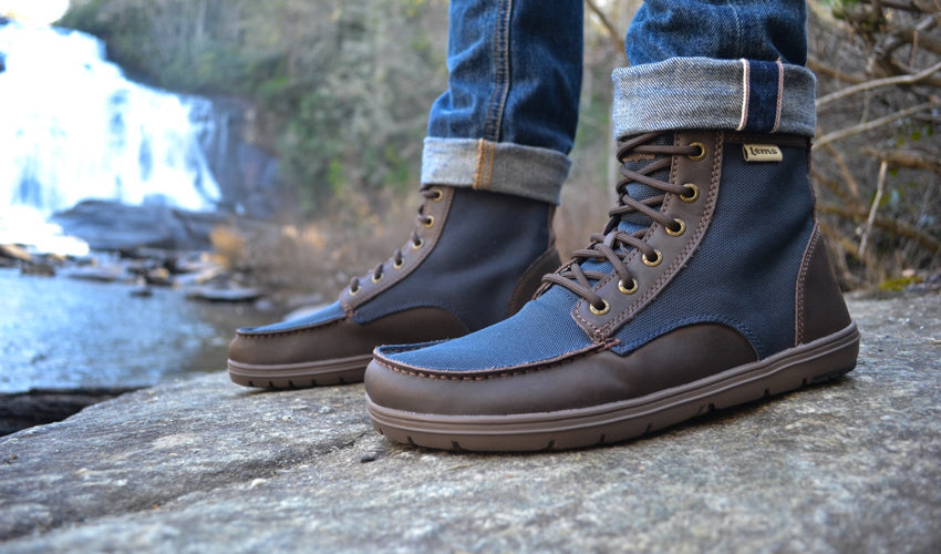 A person standing on a rocky embankment wearing Lems Boulder Boots in Nylon Navy Stout and taking in a waterfall in the background