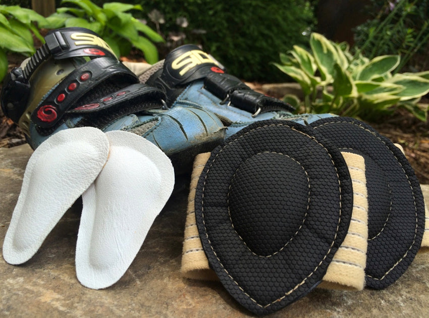 A pair of Pedag metatarsal pads and Strutz foot pads propped up in front of a pair of conventional road cycling shoes