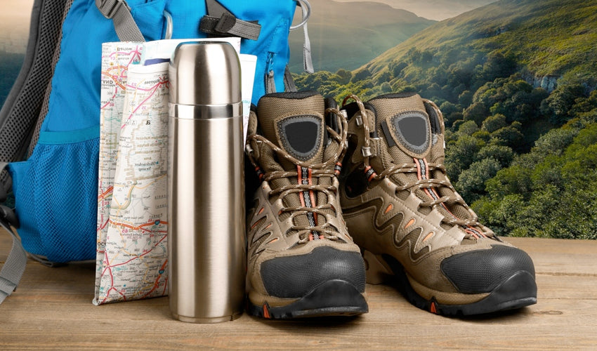 A collection of hiking gear, including conventional hiking boots, thermos, topographical map, and backpack