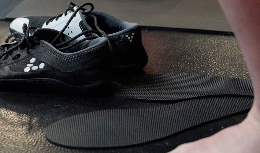 A pair of Naboso insoles sitting on a rubber gym floor with a pair of Vivobarefoot shoes nearby