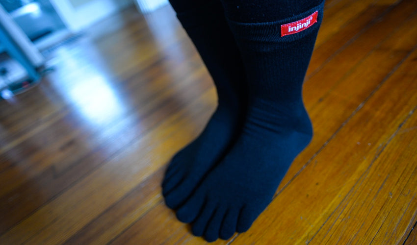 A person wearing Injinji toe socks and preparing to perform home care foot exercises
