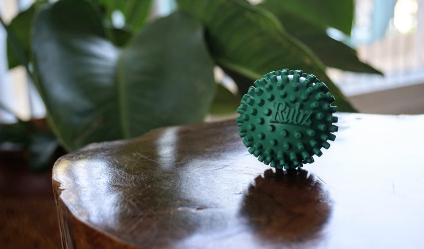 A close-up image of a Rubz foot massage ball sitting on a coffee table made from a tree stump