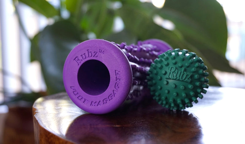 Rubz massage roller and ball sitting on top of a wood table with a large plant in the background