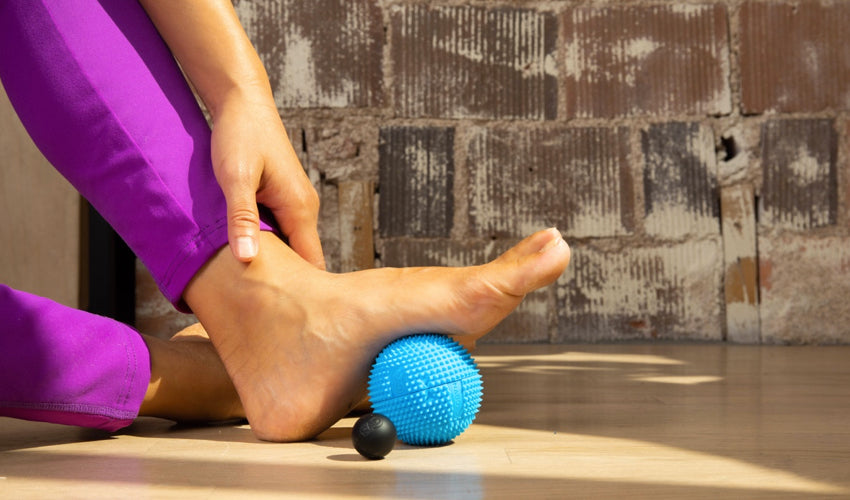 Barefoot person seated on a wood floor with left foot resting on top of a Naboso Neuro Ball with Micro Round positioned in front