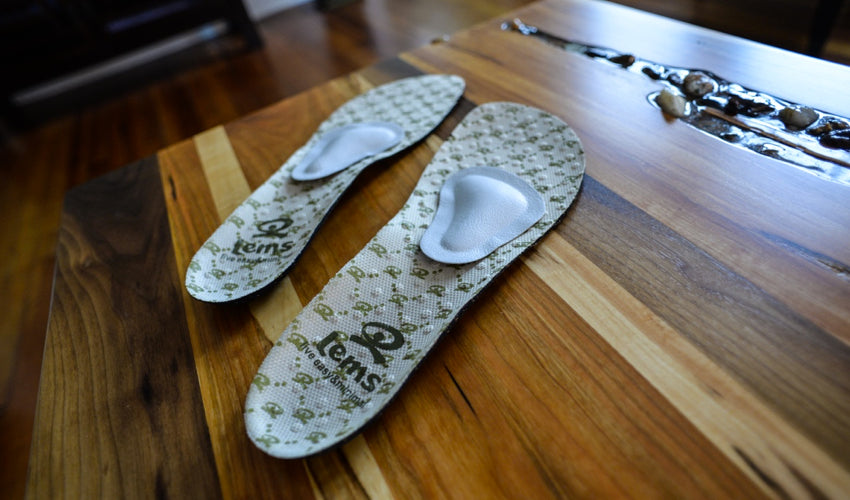 A pair of Lems Shoes insoles and Pedag metatarsal pads sitting on top of a beautiful coffee table
