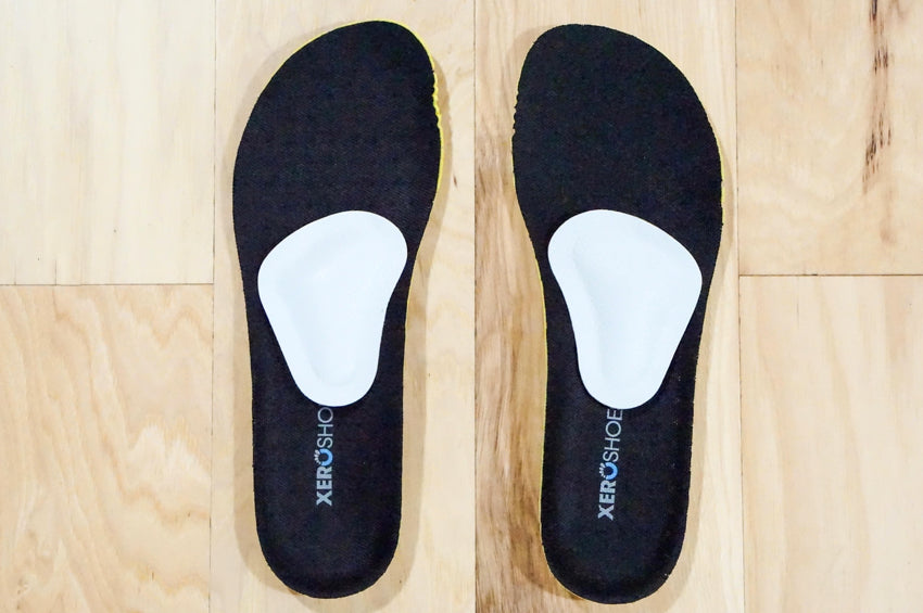Top down view of a pair of Pedag metatarsal pads mounted on black Xero Shoes insoles