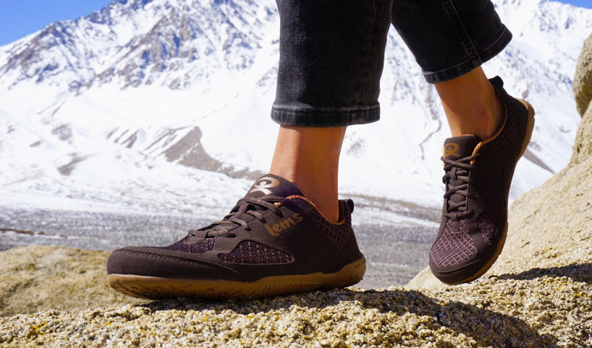A person walking in Lems Primal 2 Brown shoes with snowy mountains in the background