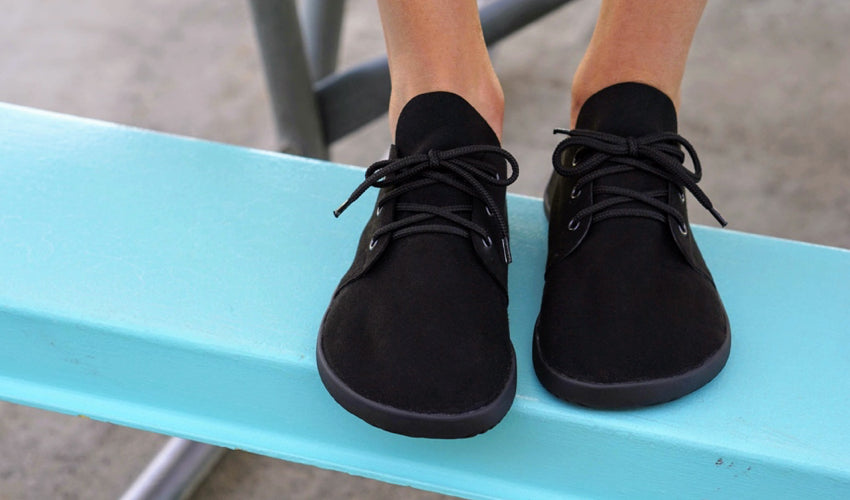 Person wearing wide toe box Ahinsa Bindu Bare Black casual shoes sitting on a picnic table