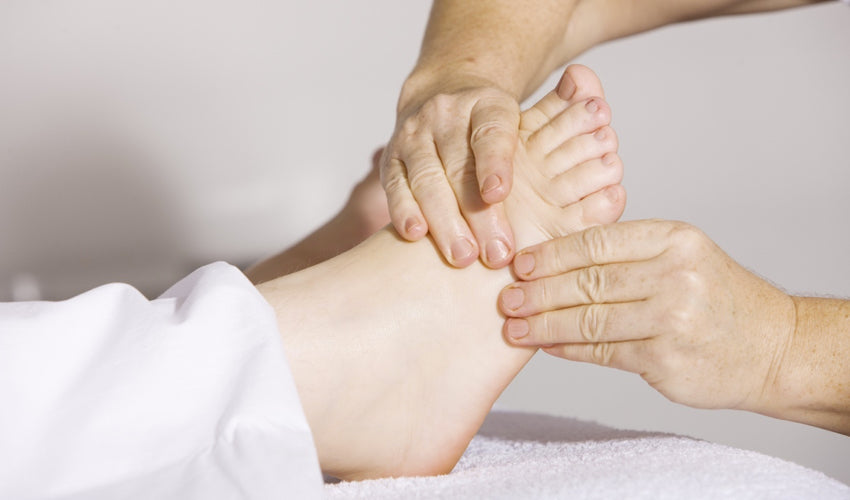 Foot care provider performing a manual treatment technique on a patient's foot