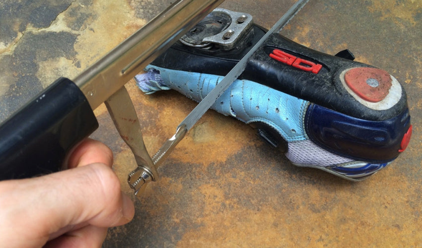 Severing through the sole plate of a conventional road cycling shoe with a hacksaw