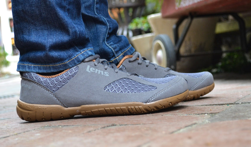 Close up view of a pair of Lems Primal 2 Slate shoes with cobblestones in the foreground