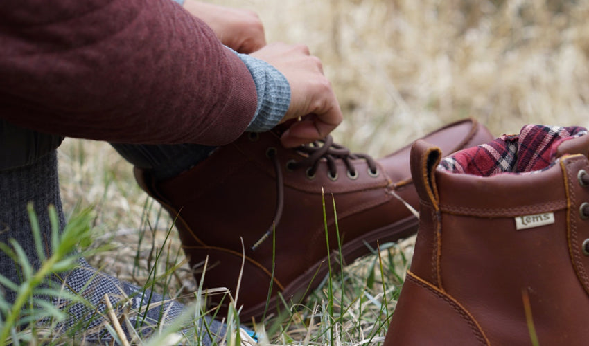 A person seated in a grassy meadow tying the laces of a pair of Lems Boulder Boots in Leather Russet