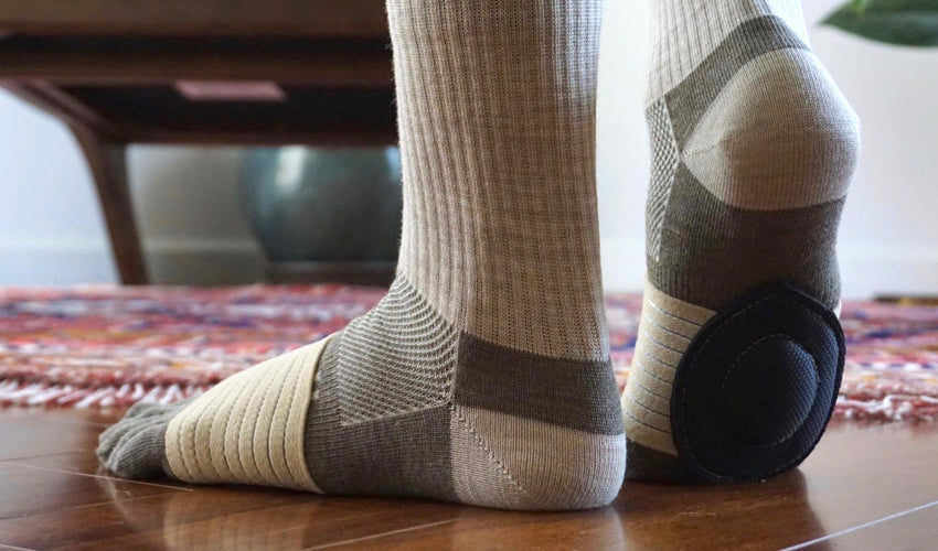 Close-up view of a person in toe socks wearing Strutz Rx foot pads in Beige/Black