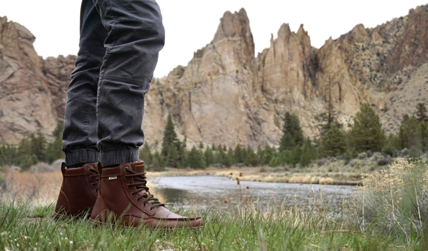 Person wearing the Lems Boulder Boot in Leather Russet and standing in a grassy field with mountains and stream in the background