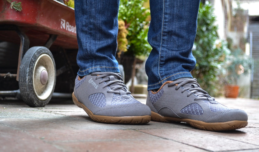 Oblique view of Lems Primal 2 Slate shoes with a red wagon in the background
