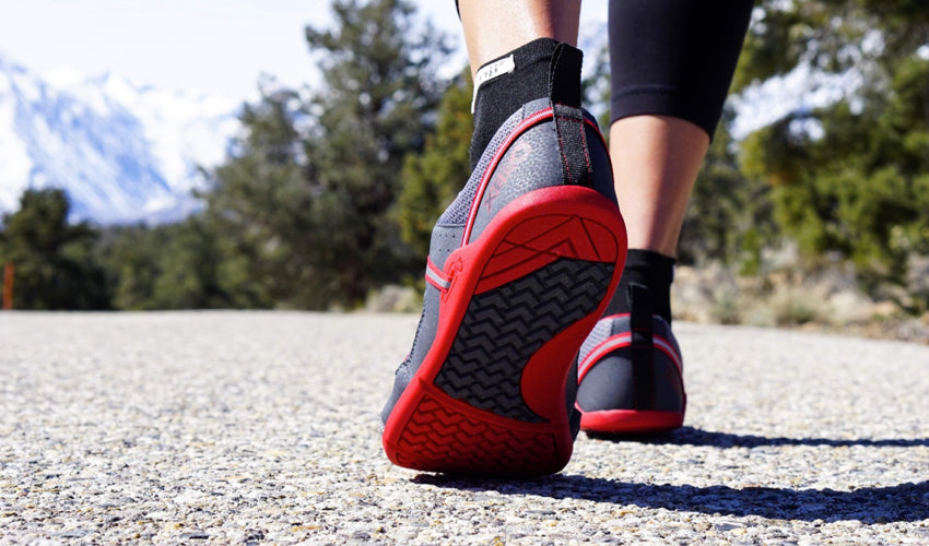 Close-up view from behind of a person walking on pavement in Xero Prio athletic shoes