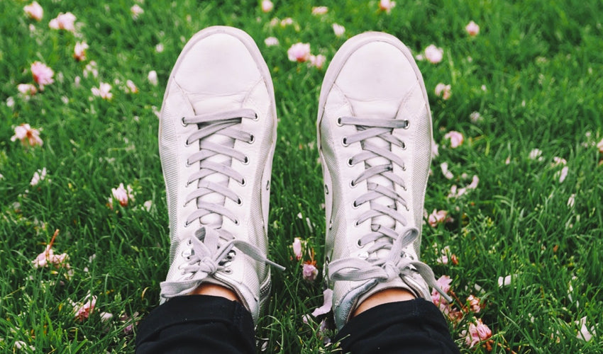 A top-down view of a pair of tapering toe box white shoes with a meadow in the background