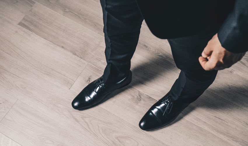 Top-down view of a pair of conventional black dress shoes with tapering toe boxes