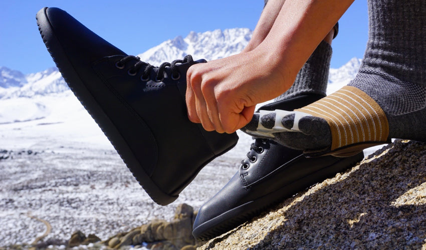 A hiker wearing Strutz Pro Brown foot pads and Correct Toes toe spacing pads putting on Ahinsa Trek Bare Ankle Black boots