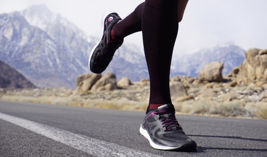 Athlete in zero drop athletic shoes and compression toe socks running on the road with large mountains in the background