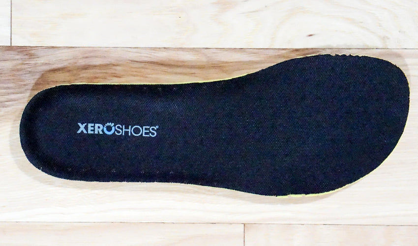 A Xero Shoes insole sitting on top of a light wood floor