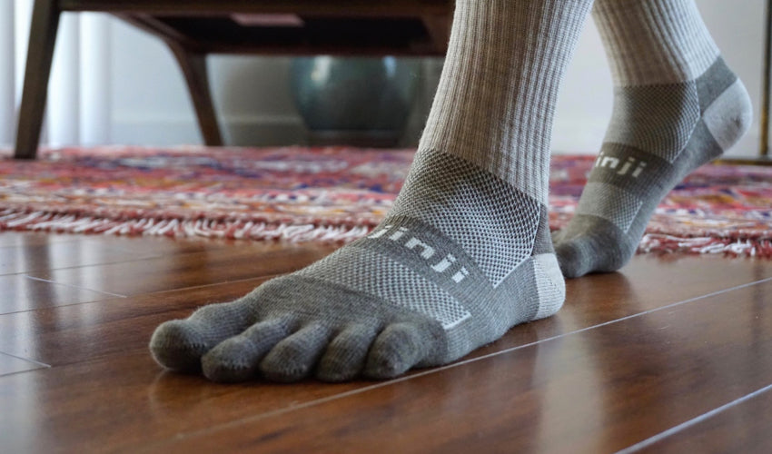 Pair of feet wearing toe socks with well-aligned big toes, helping to boost intrinsic foot muscle strength