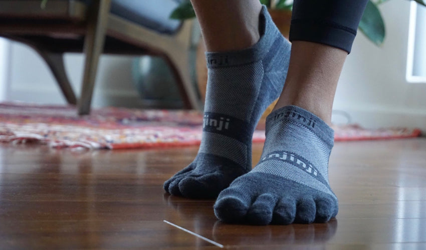 Pair of healthy feet wearing toe socks with a well-aligned big toe helping to enable natural arch support