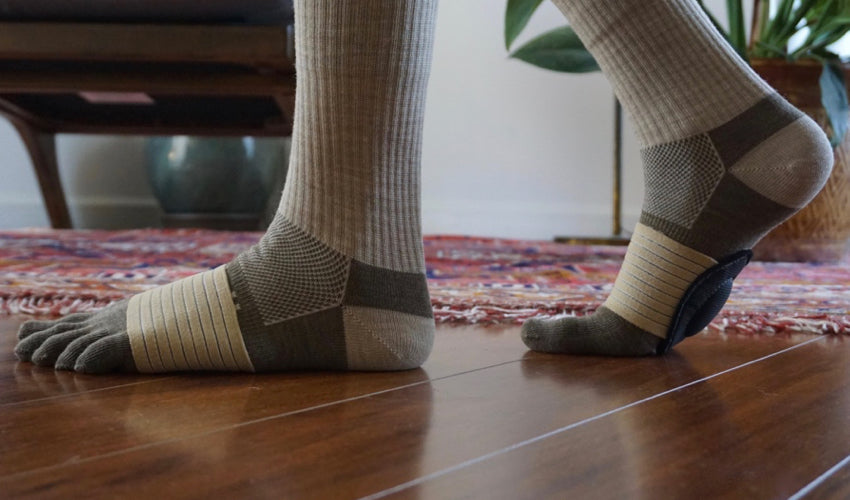 Side view of a person wearing Injinji toe socks and Strutz foot pads indoors, on wood flooring