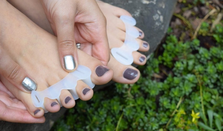 Person applying Correct Toes Original toe spacers in a garden setting