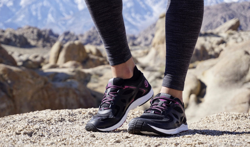 A trail walker posing in her Topo ST-2 athletic shoes in Black/Raspberry with snowy mountains in the background