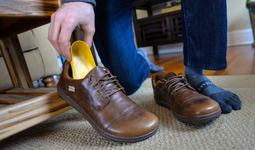 Person putting a Tuli's heel cup into a pair of Lems Nine2five Mocha shoes