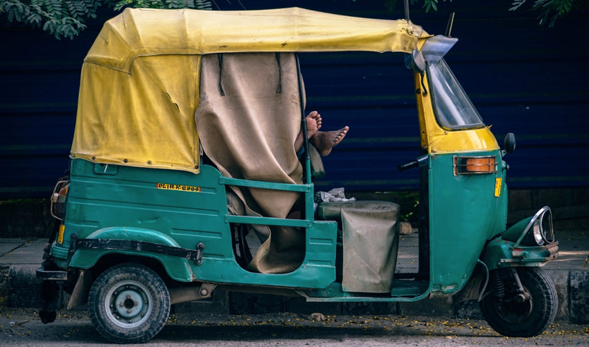 The feet of an Indian autorickshaw driver who is lying in repose inside his vehicle