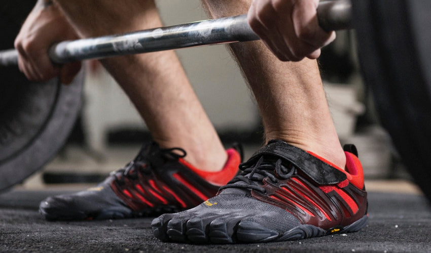 A powerlifter, wearing Vibram FiveFingers shoes, preparing for a lift