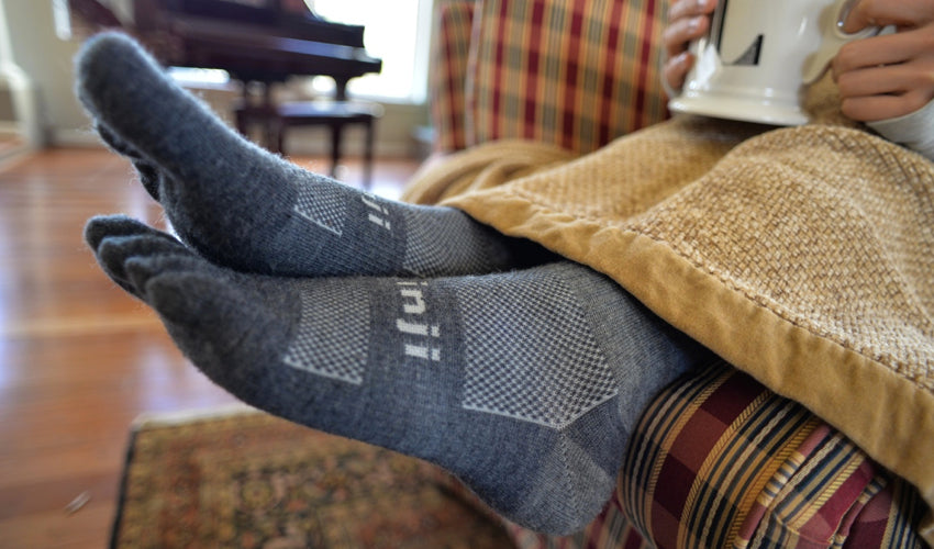 Injinji Original Weight Crew Wool Charcoal toe socks poking out from beneath a blanket