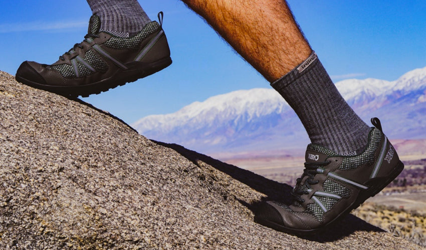 Male hiker wearing Xero TerraFlex trail shoes climbing a boulder with mountains in the background