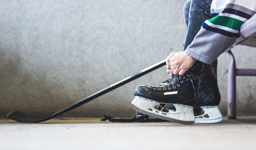 Young hockey player sitting on a bench and lacing up an ice skate