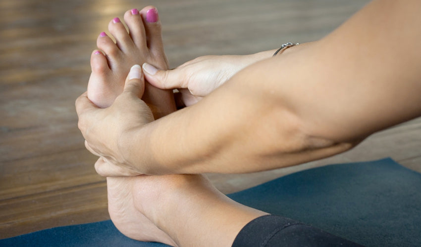 A person performing a foot self-care exercise at home