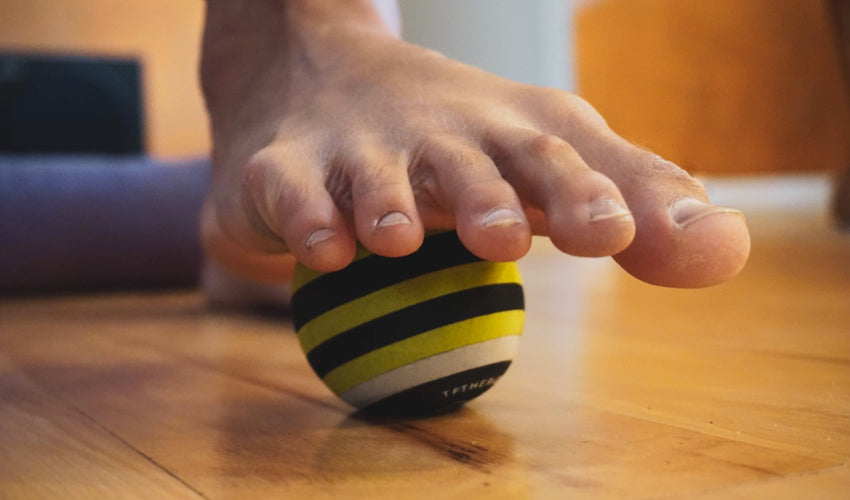 A bare foot resting on top of a striped massage ball