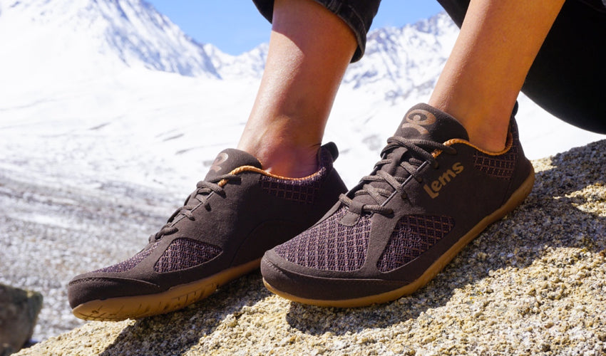 Female hiker wearing Lems Primal 2 Brown minimalist shoes