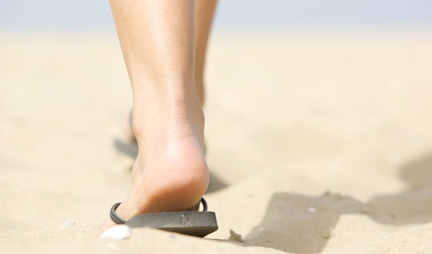 Shot from behind of a person wearing flip-flops and walking over beach sand