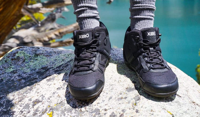 A hiker, standing on a rock and with a green lake in the background, wearing Xero DayLite Hiker EV Black hiking boots