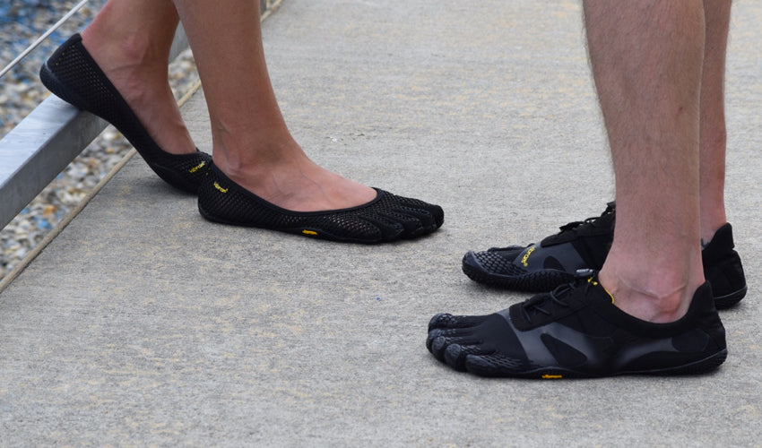 Two people wearing Vibram FiveFingers shoes and standing on a concrete platform