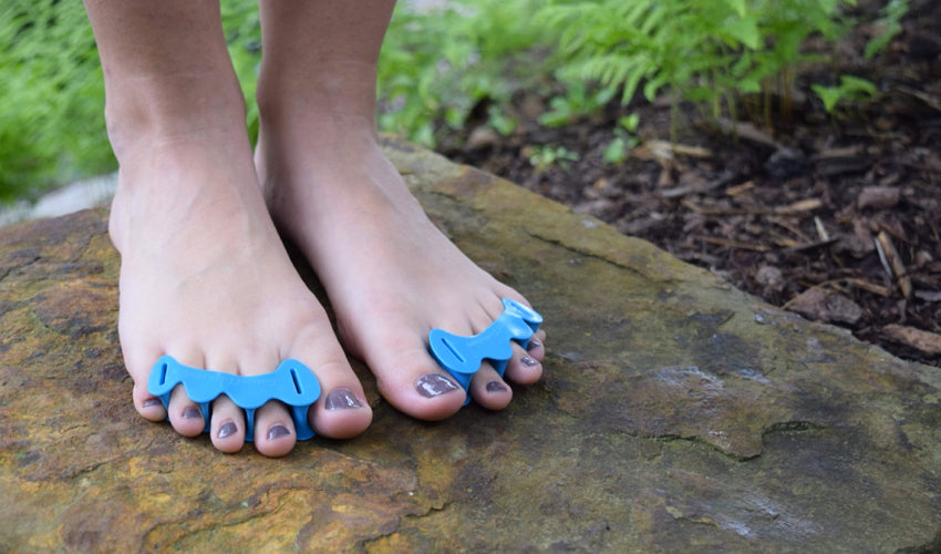 Correct Toes Aqua toe spacers on the bare feet of a person standing on a stone step