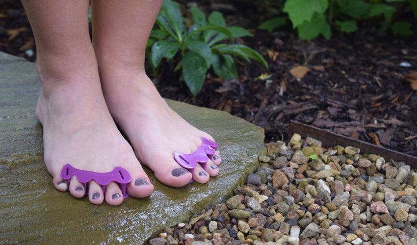A person wearing Correct Toes Plum toe spacers and standing on a wet stone