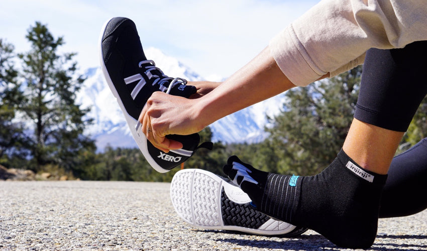 A person, wearing a spate of natural footgear, donning a pair of Xero Prio athletic shoes with snowy mountains in the background