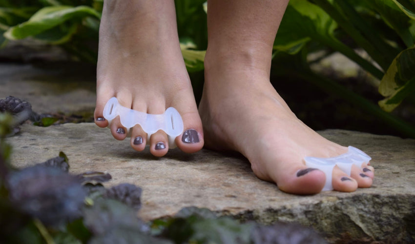 A barefooted person wearing Correct Toes Original toe spacers walking over flat stones in a garden setting