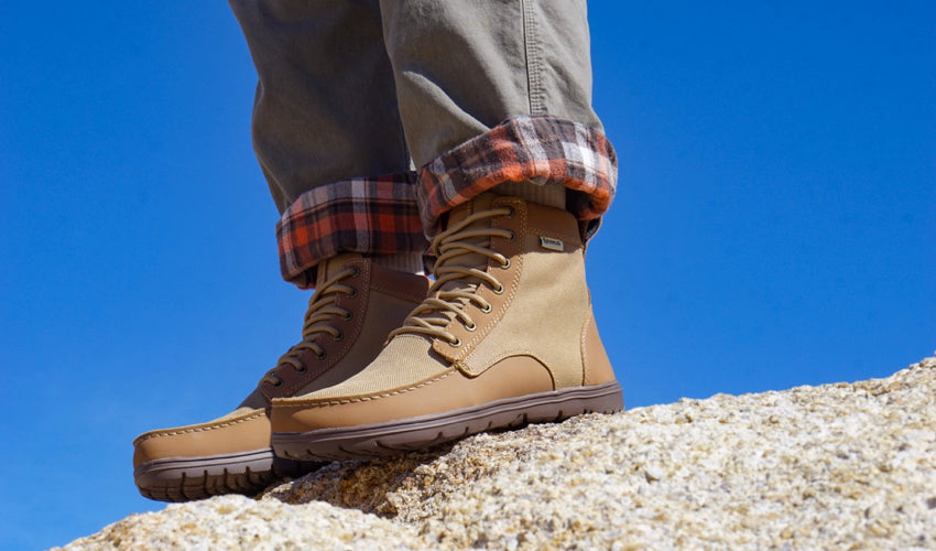 A hiker, poised on a large rock and with a deep blue sky in the background, wearing Lems Boulder Boots.
