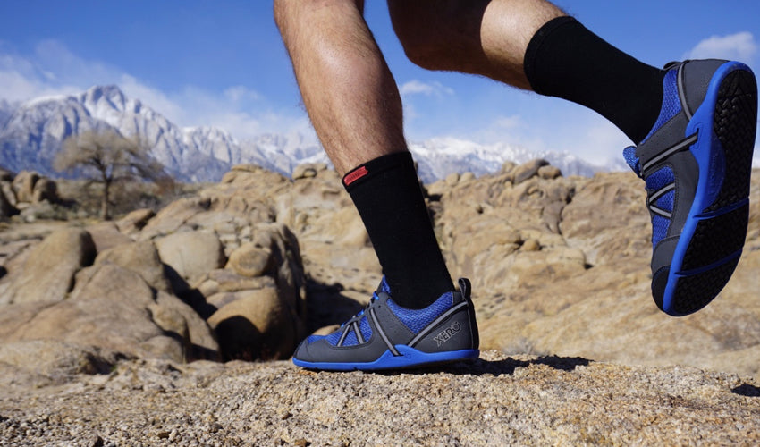 A trail runner in mid-stride wearing Xero Prio Lightning Blue athletic shoes